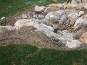 Landscaping in Bountiful Utah, landscaper installing, Huge rock boulder retaining walls, rock walls, Retaining, double pump energy efficient water features, walls, landscaping, Belgard natural gas fire pit, Belgard Mega Laffit Paver patio around the pool, Belgard Paver walls in Belair with belair caps, Paver fire pits, trees, topsoil, sod from bio grass sod farms, Landscape construction, landscaping in Bountiful, Utah